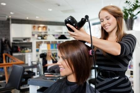 Coiffeuse en train de sécher les cheveux d'une cliente