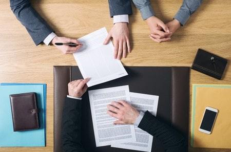 Couple en train de signer acte d'achat maison chez le notaire